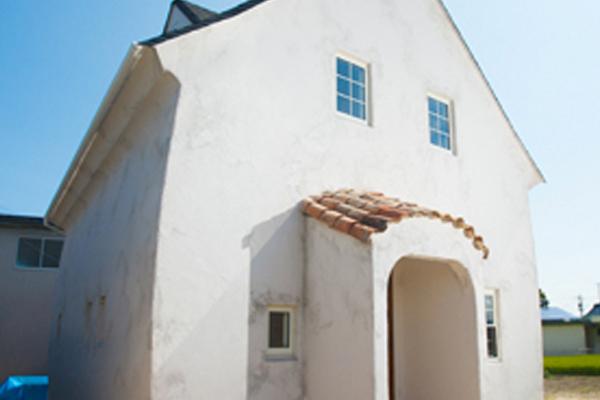 とんがり屋根とぽってりフォルム塗り壁のお家